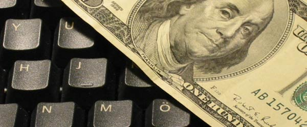 A hundred dollar bill on top of a keyboard