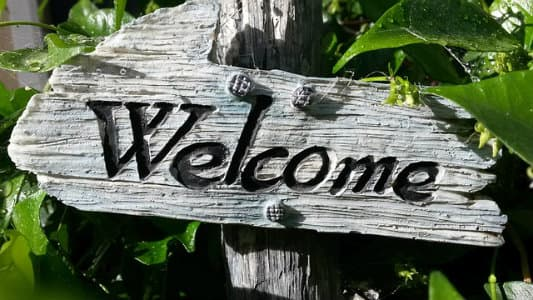 "Wooden sign in a garden with the word ""Welcome"" on it"
